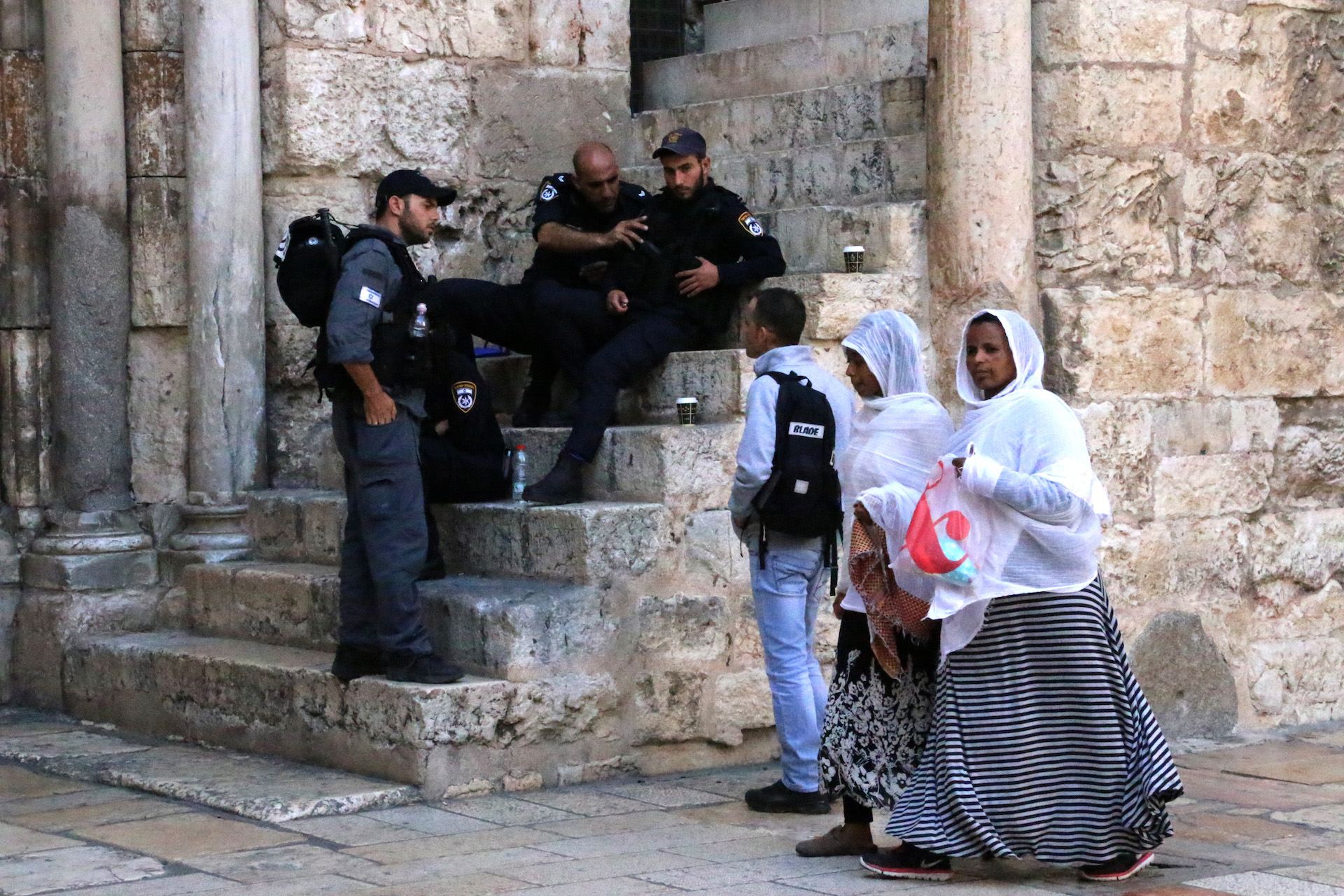 JERUSALEM, ISRAEL, MAY 29, 2016. Women on their way to the entrance of the Church of the Holy Sepulchre, where mass has just begun, while guards relax on the steps of the church. Located in the Christian Quarter of the Old City of Jerusalem. 05/29/2016. Photo by Donna M. Airoldi