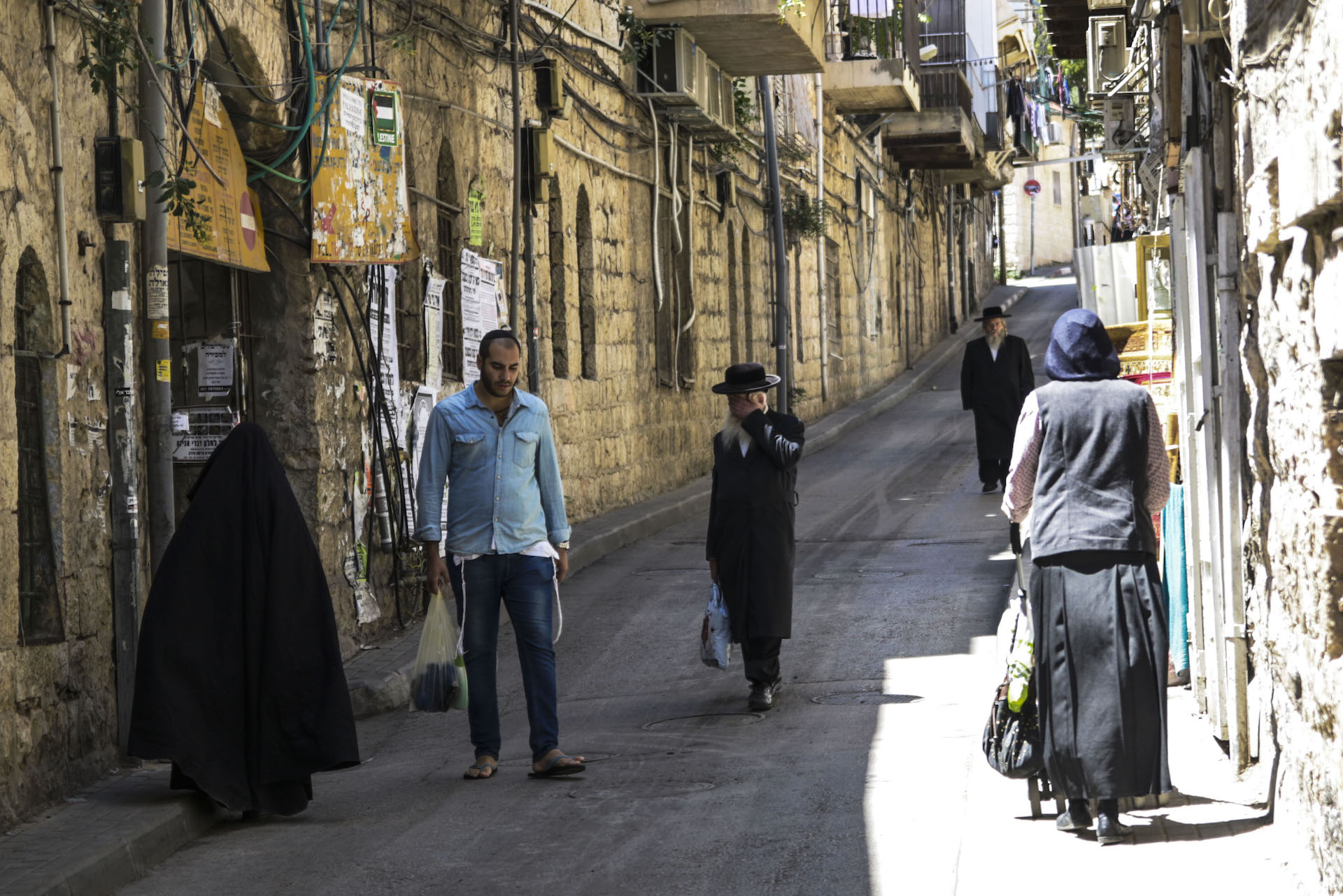 "A man moves out of the way and another covers his face as a woman in burqa-style veil walks in a street if the Mea Shearim neighborhood of Jerusalem. The ""frumkas"", a sect that claims to bring back an ancient level of modesty among the Haredi, are highly criticized by the larger community. Photo: Gustavo Martínez Contreras