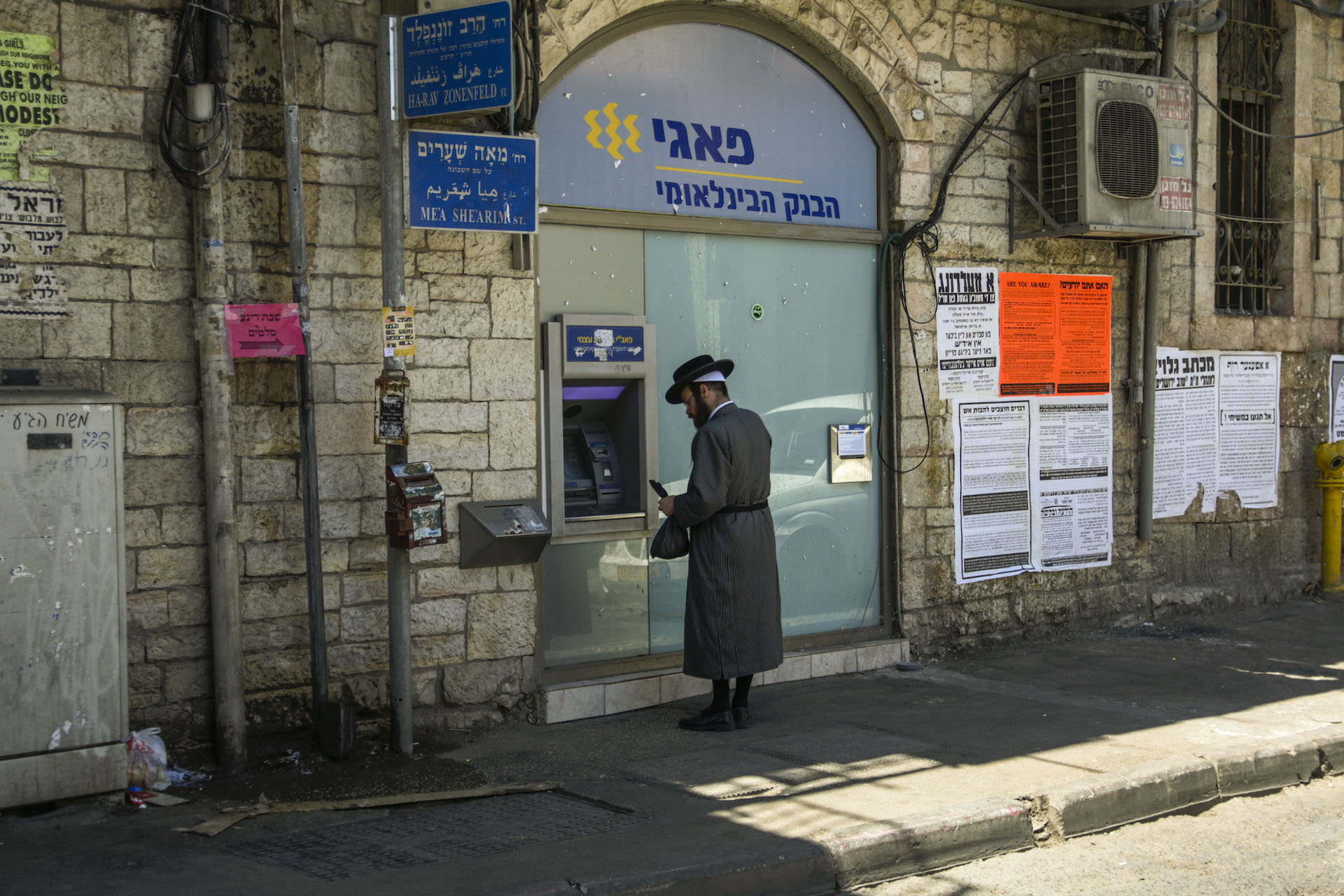A man clad in a traditional Neturei Karta outfit uses a cash machine in Jerusalem's Mea Shearim neighborhood. The Neturei Karta live among the Haredis, and mostly in the same fashion. They also hold anti-Zionist views and call for the dismantling of the Jewish State.