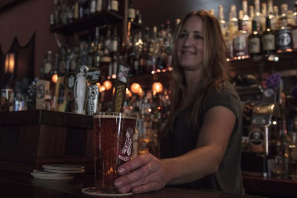 Meghan Giometti, owner of The Gibson bar in Williamsburg, Brooklyn, serves a beer to a customer. (Photo by: Anna Brooks)