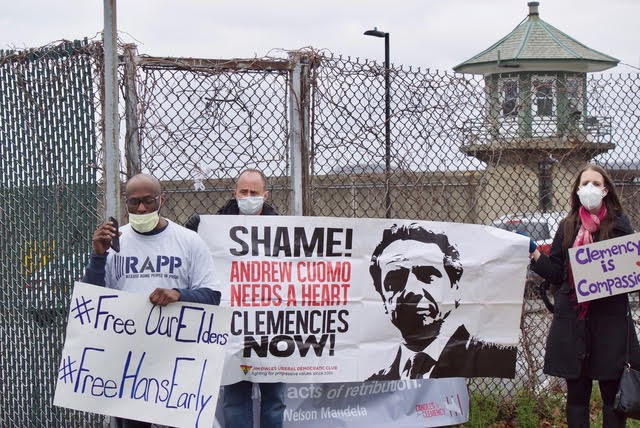 """People stand outside of Sing Sing Correctional Facility with signs that read """"Free Our Elders"""" and """"Clemency Now."""""""