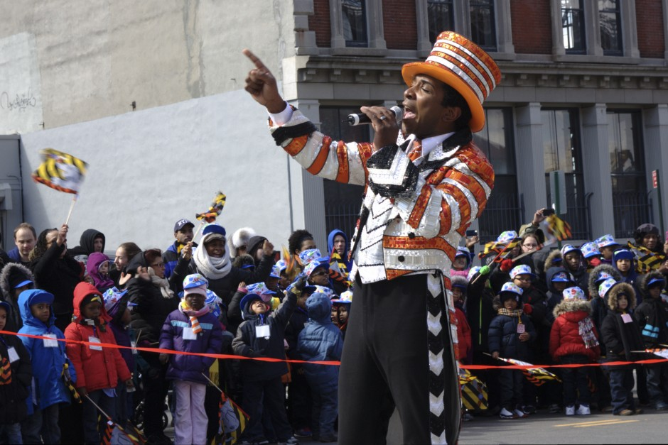 An announcer, decked out in circus finery, speaks to the crowd which lined the street to watch the elephants.