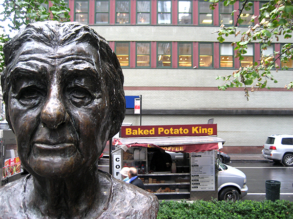 Baked Potato vendor in background of a statue bust.