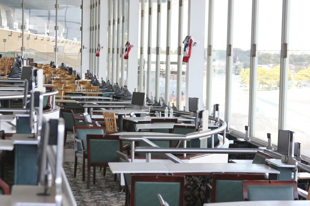 The seats overlooking the Aqueduct racetrack stand empty—live horse racing has moved to the Belmont track on Long Island. The Aqueduct features remote horse betting along with slot machines and electronic table games.