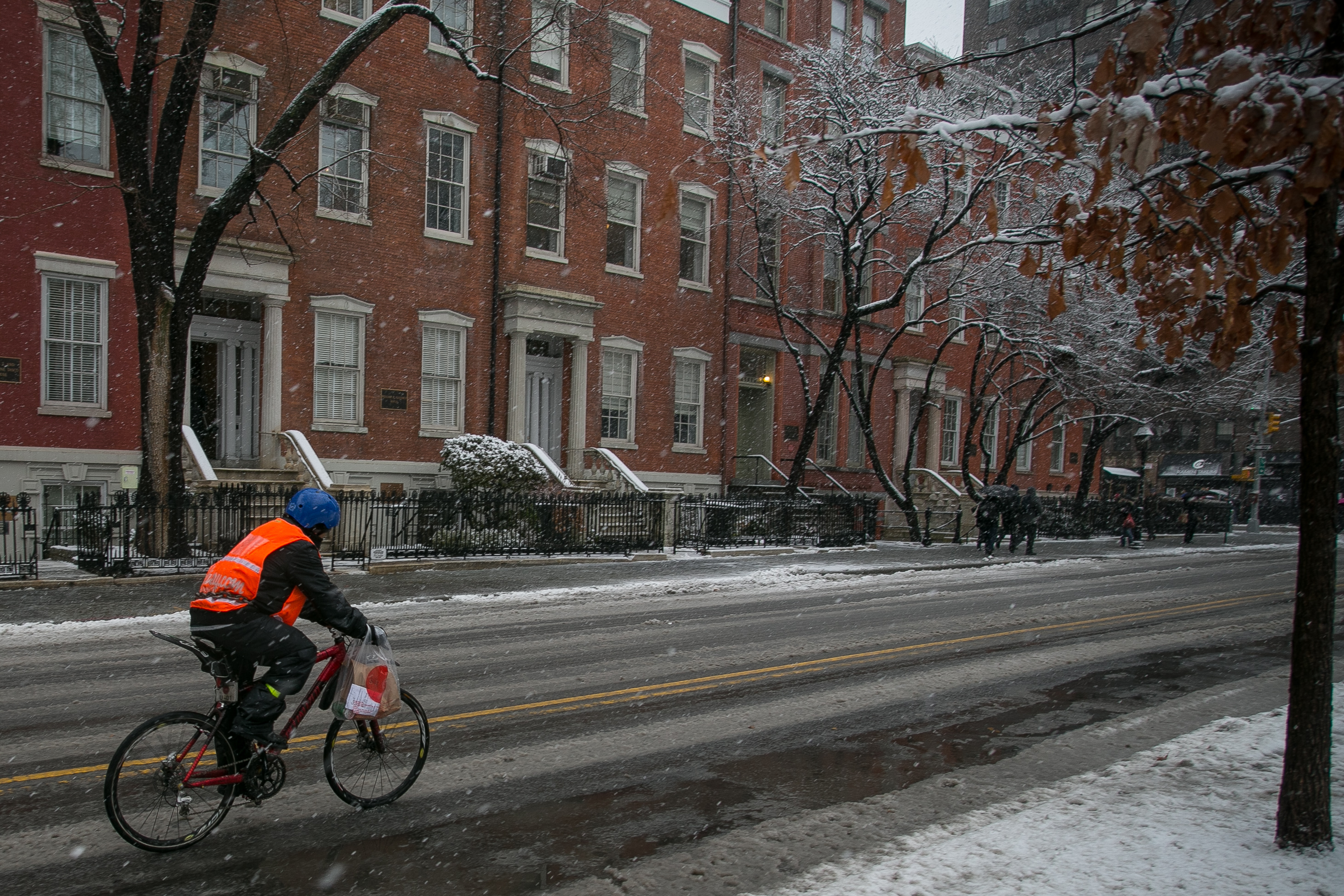 A deliveryman rides through a snow storm during the lunch rush in Greenwich Village.