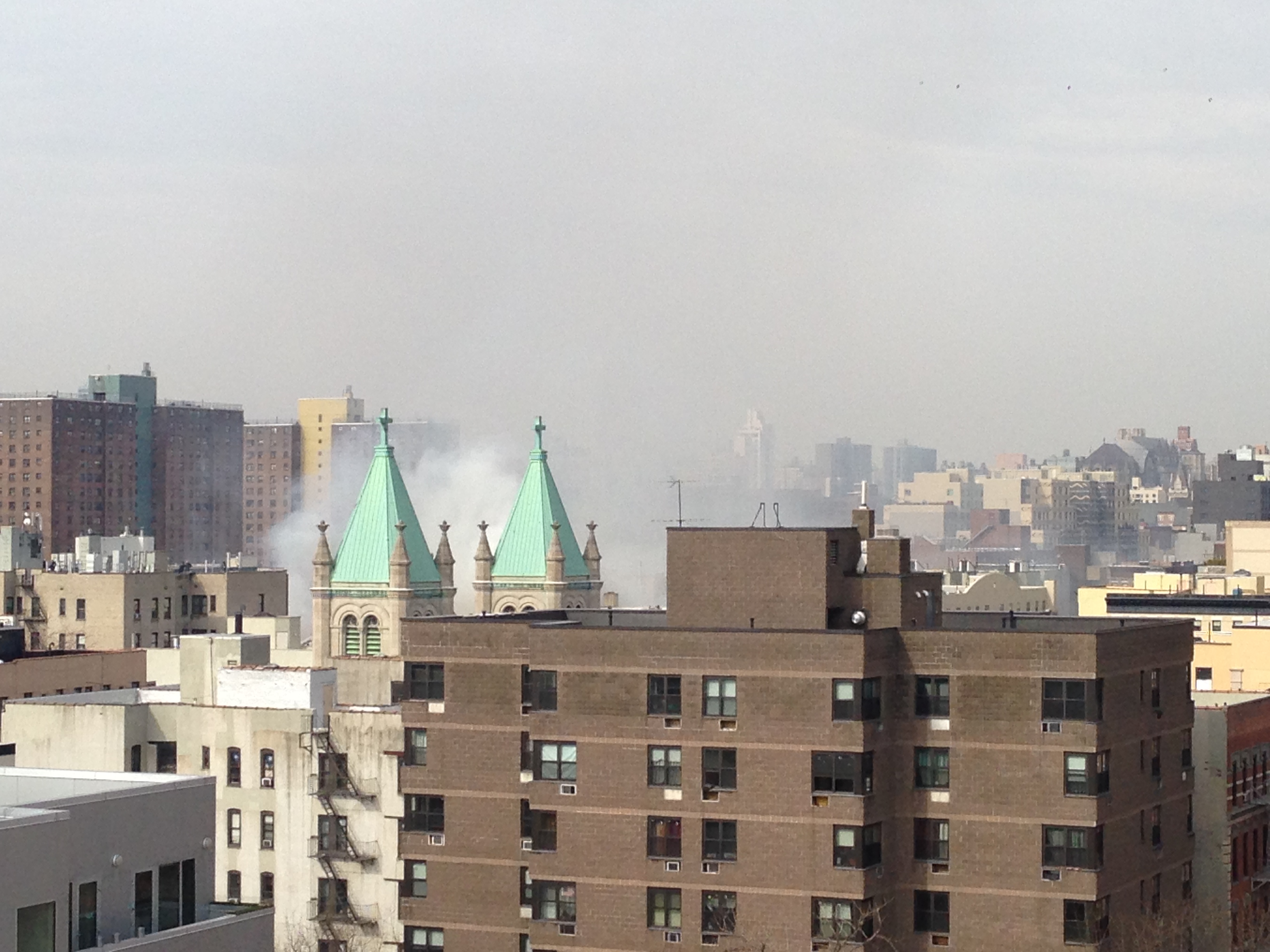 Smoke rises from a fire that resulted after an explosion in East Harlem on Wednesday, March 12. The explosion, which was caused by a gas leak, led to the collapse of two buildings.