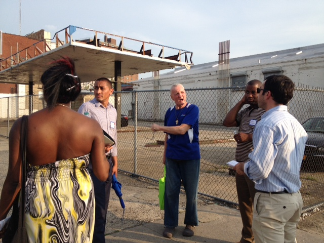 A group of residents and developers surveys an abandoned gas station on 138th St. on June 26.