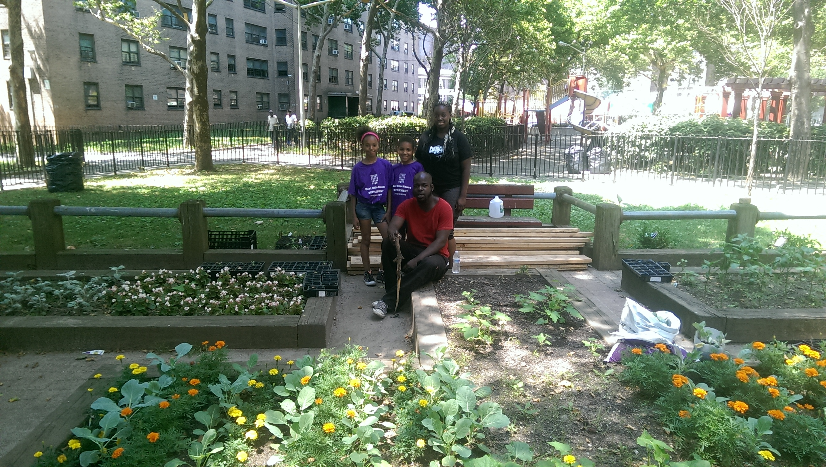 Millbrook Houses residents Von Franklin (seated), Shella Hair and two young volunteers in the community garden near where a new greenhouse will be constructed.