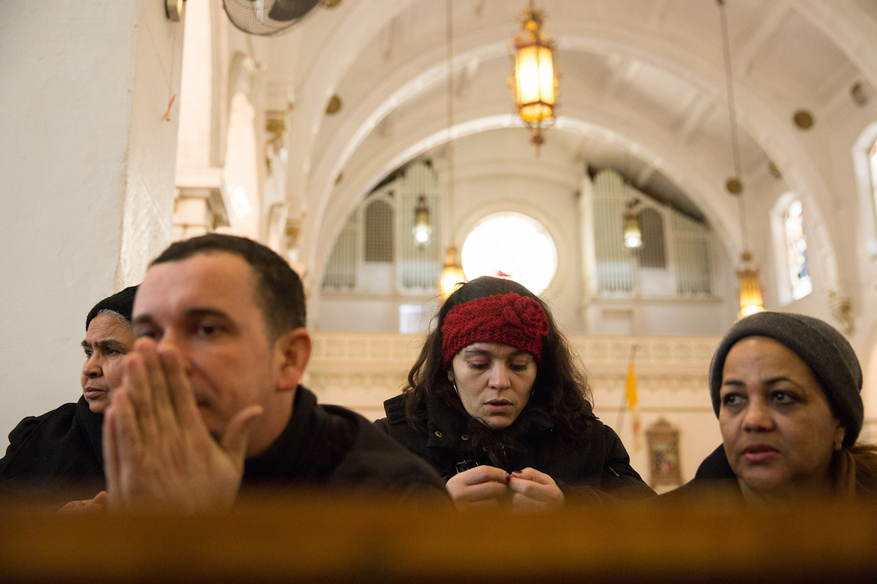 Parishioners at the Church of St. Roch hold a Sunday vigil.