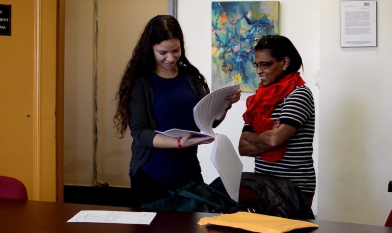 A Senior Homelessness Project reviews paperwork with a client at Bronx housing court.