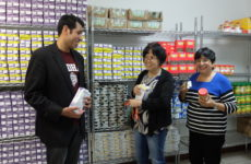 Volunteer teachers Yohan Garcia, Puri Padilla, and Adela Paredes help out at St. Jerome H.A.N.D.S.' weekly food pantry for immigrants and families in need.  Photo: Allyson Escobar