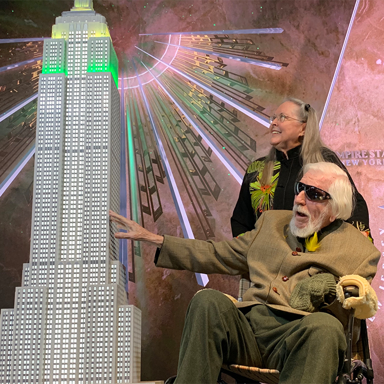 Caroll Spinney reaches out to a model of the Empire State Building while posing with wife, Debra