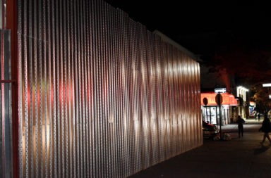 Corrugated-metal wall around the former site of a gas station near Newkirk Plaza in Brooklyn.