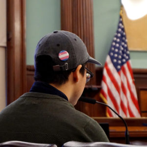 A City Council hearing speaker wears a trans flag pin.