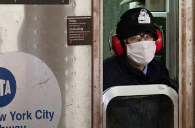 Subway conductor wears mask.