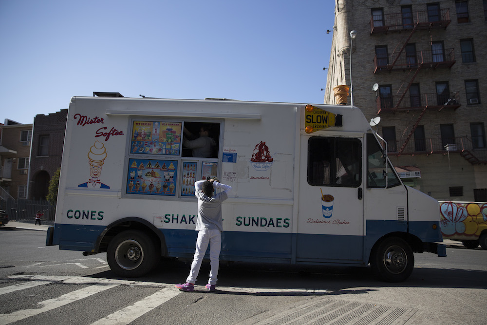 A boy buys an ice cream cone from a Mister Softee truck parked on Seneca Avenue in the Bronx (photo by Jessica Bal).