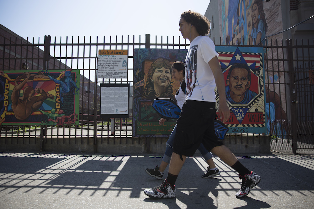 Pedestrians pass by Hunts Point Avenue murals created by Hunts Point students in collaboration with the nonprofit organization Groundswell (photo by Jessica Bal).