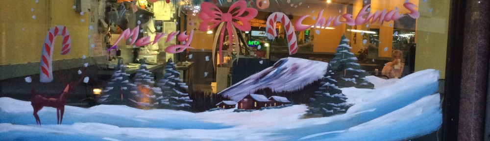 "A window with painted on snow, trees, bows and candy canes. It reads ""Merry Christmas"""